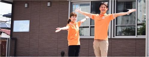 職場の前で両手を広げるスタッフの写真